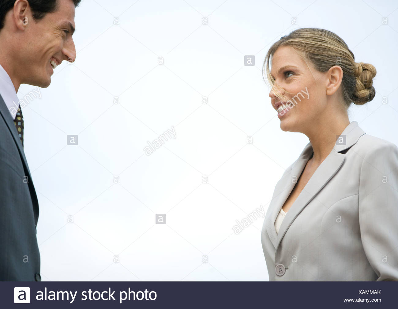 Businesswoman and businessman smiling at each other - Stock Image
