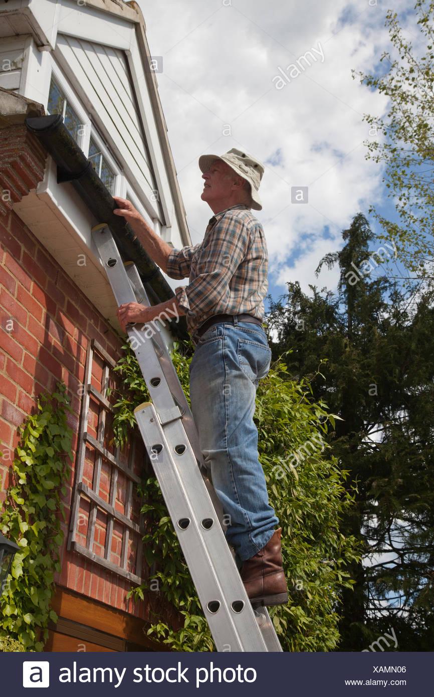 Senior man on ladder fixing gutter - Stock Image