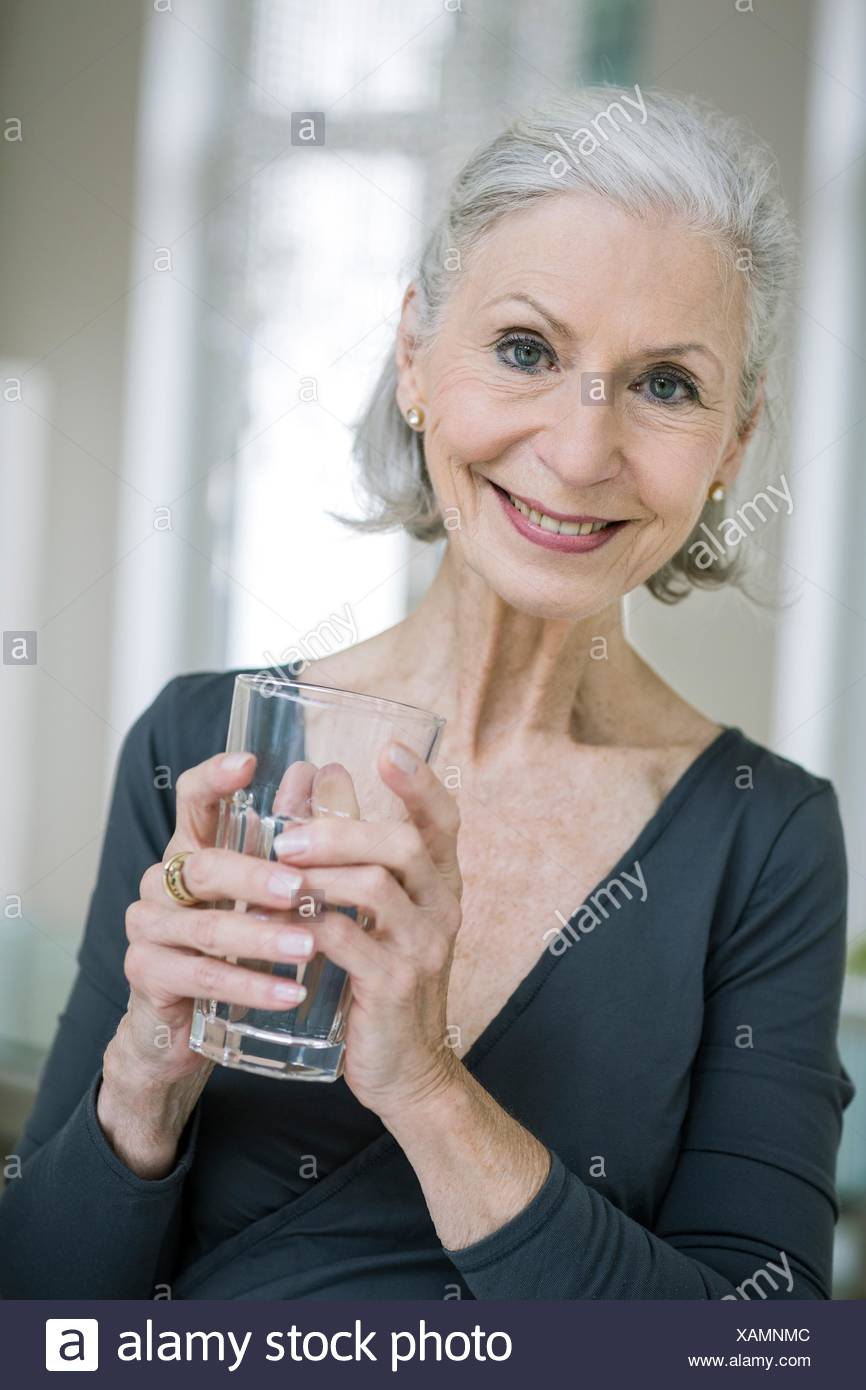 Portrait of gray haired senior woman holding tumbler looking at camera smiling - Stock Image