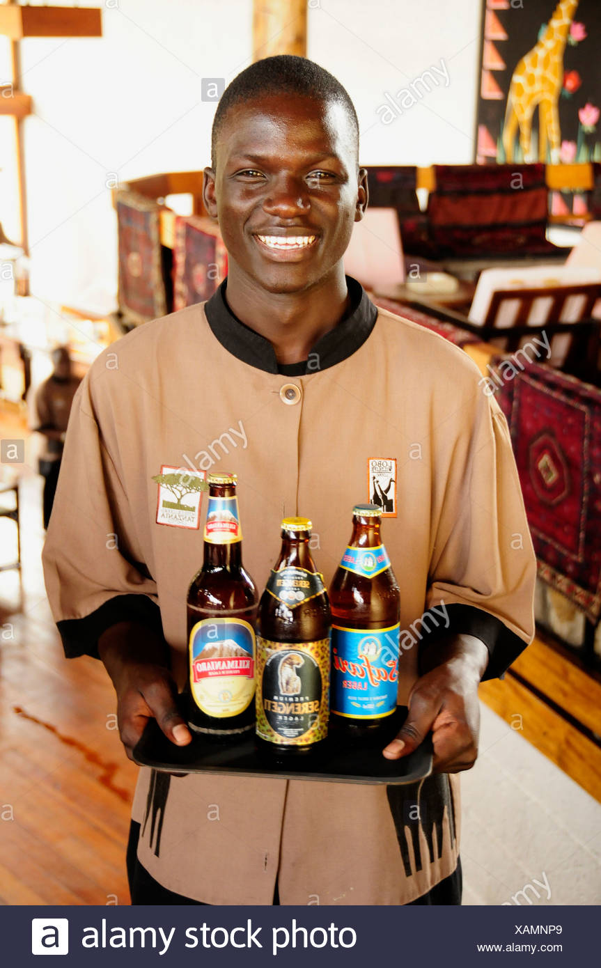 Waiter carrying the three most popular beers in Tanzania, Serengeti, Kilimanjaro and Safari, Lobo Wildlife Lodge - Stock Image