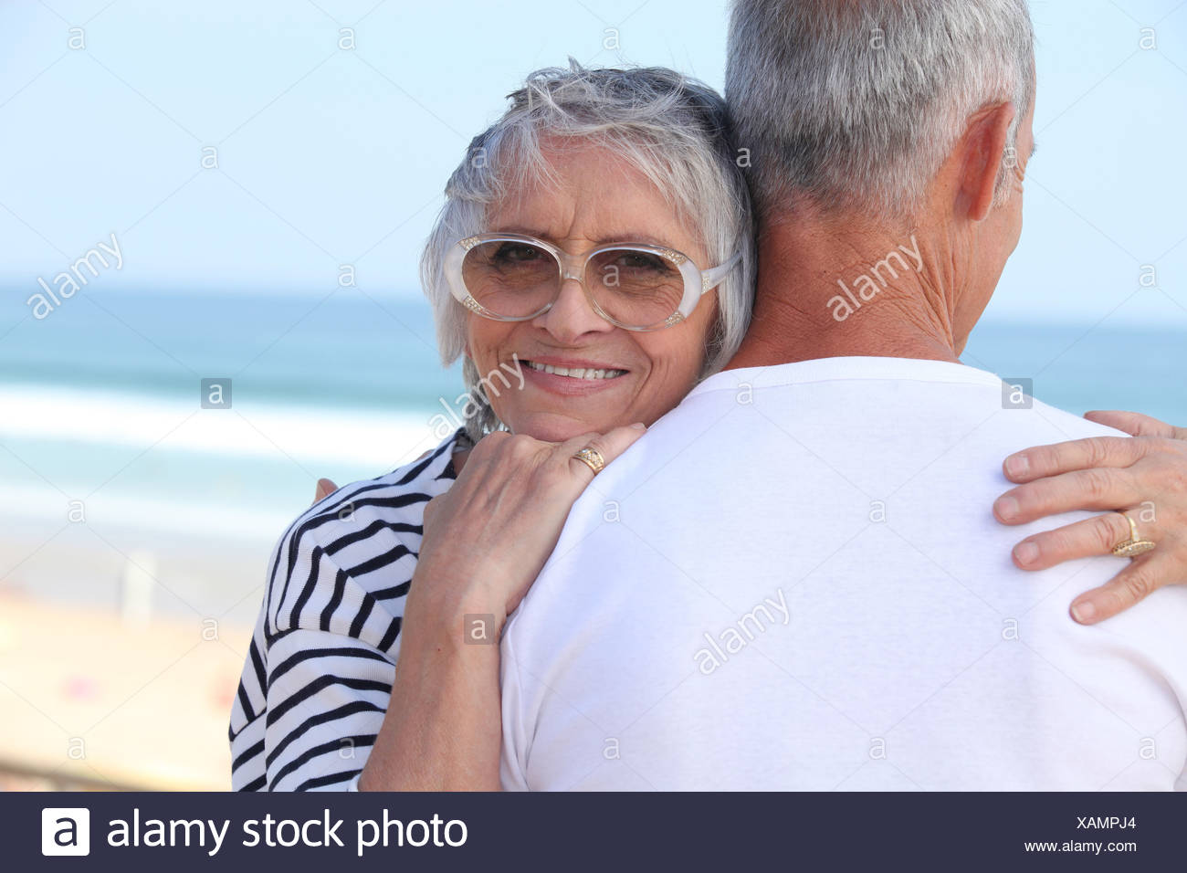 Elderly couple hugging by a beach - Stock Image
