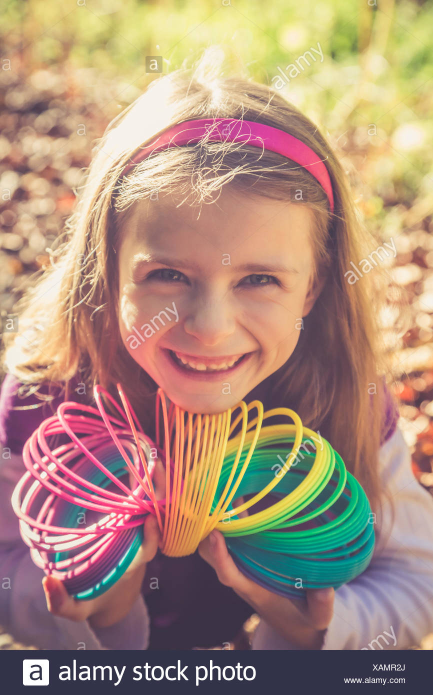 Portrait of smiling little girl with spiral in prismatic colours - Stock Image