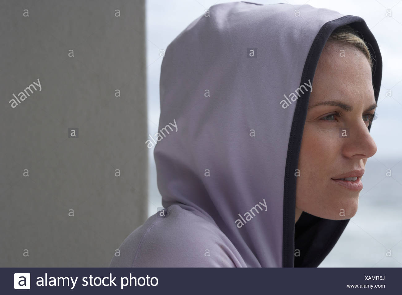 Woman wearing hooded top close up side view - Stock Image