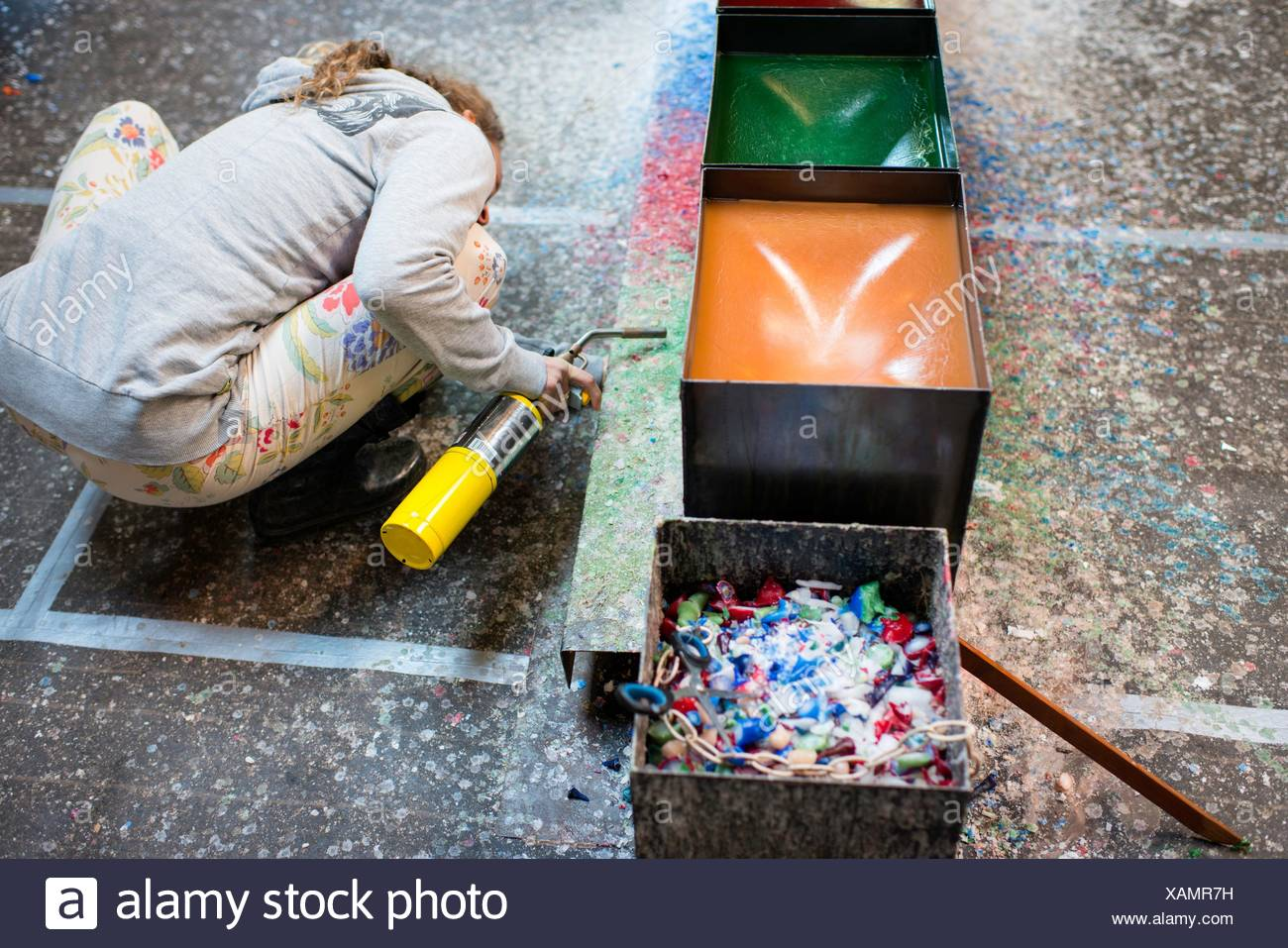 Female candlemaker crouching to melt wax with blowtorch - Stock Image