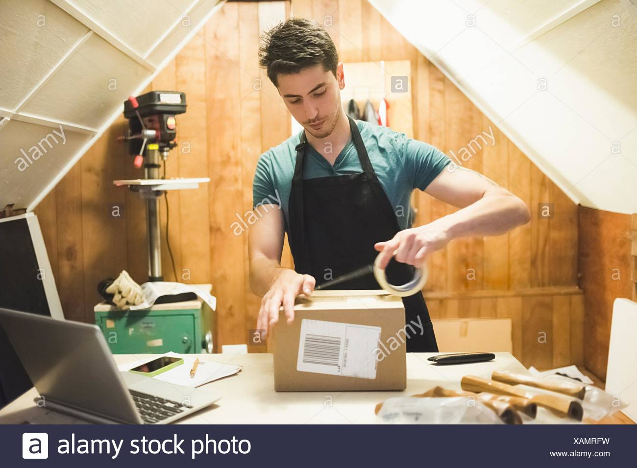 Young man using sticking tape to prepare package for delivery - Stock Image