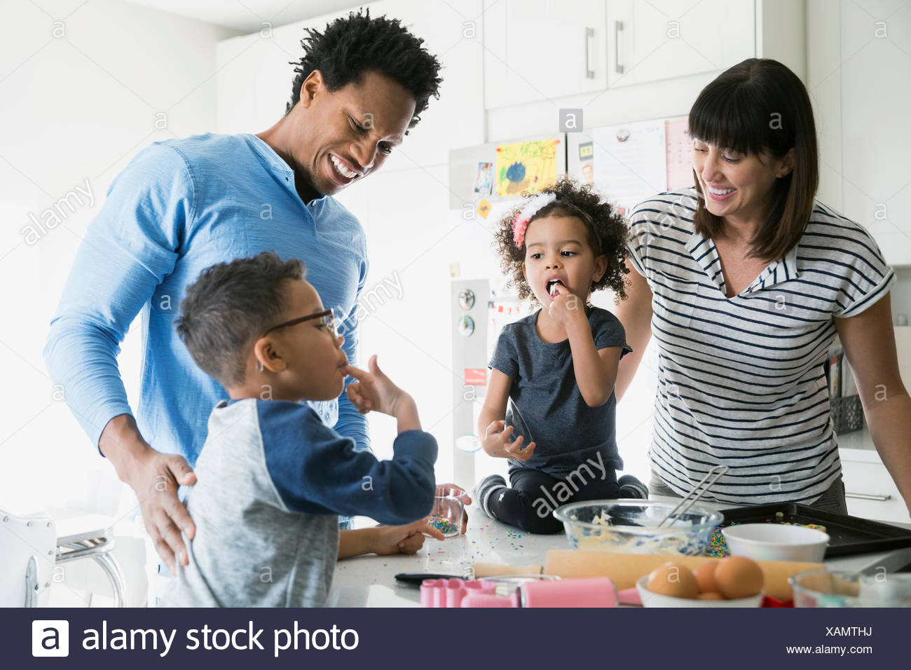 Brother and sister baking tasting cookie dough - Stock Image