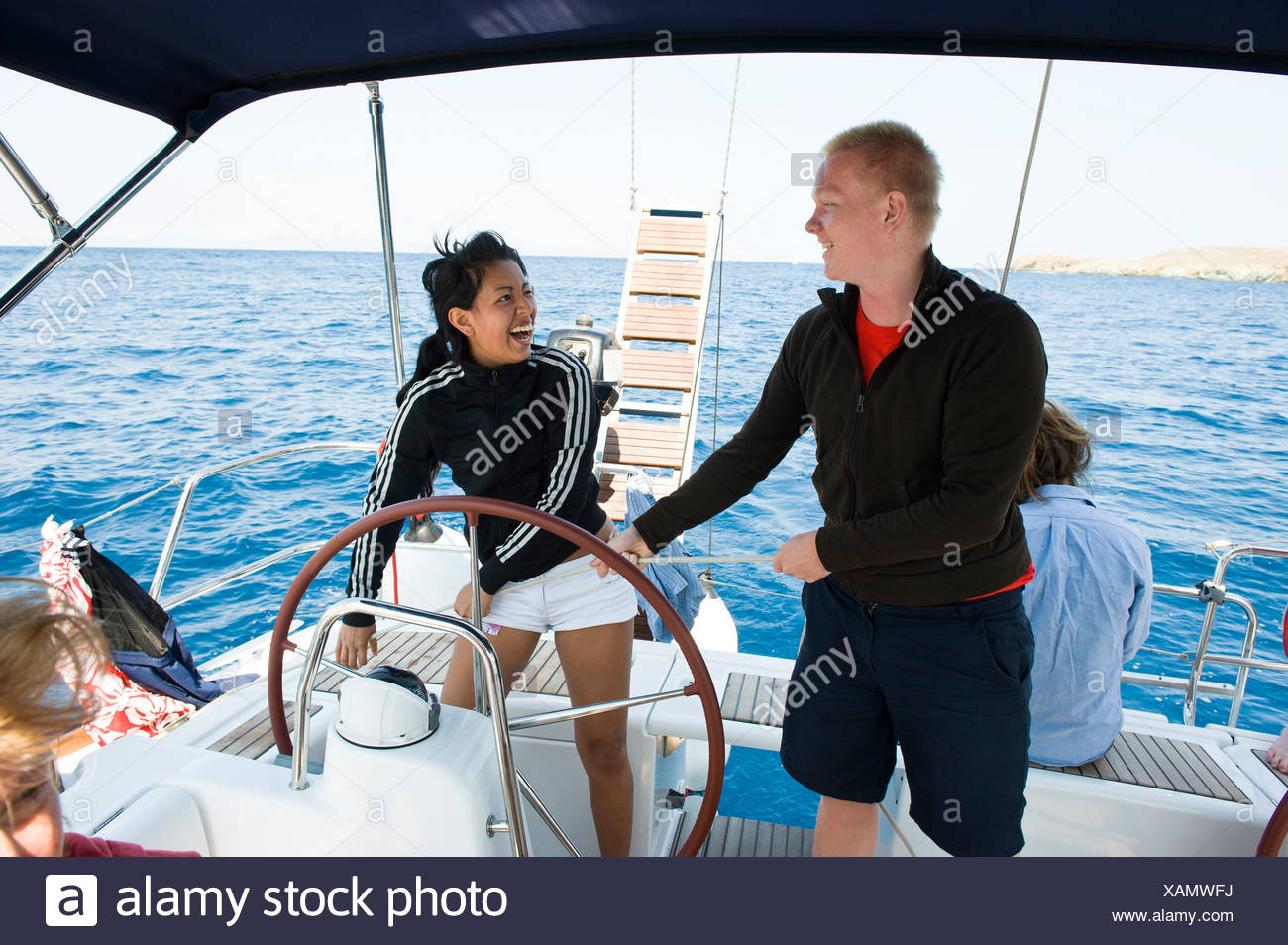 Happy teenage boy and girl steering a sail boat in the sea - Stock Image
