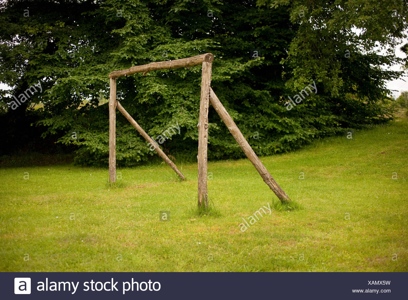 Wooden goal post on grass - Stock Image