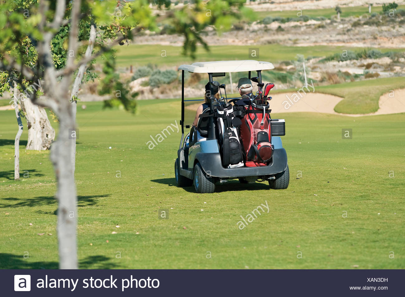 Cyprus, Man and woman sitting in golf cart - Stock Image