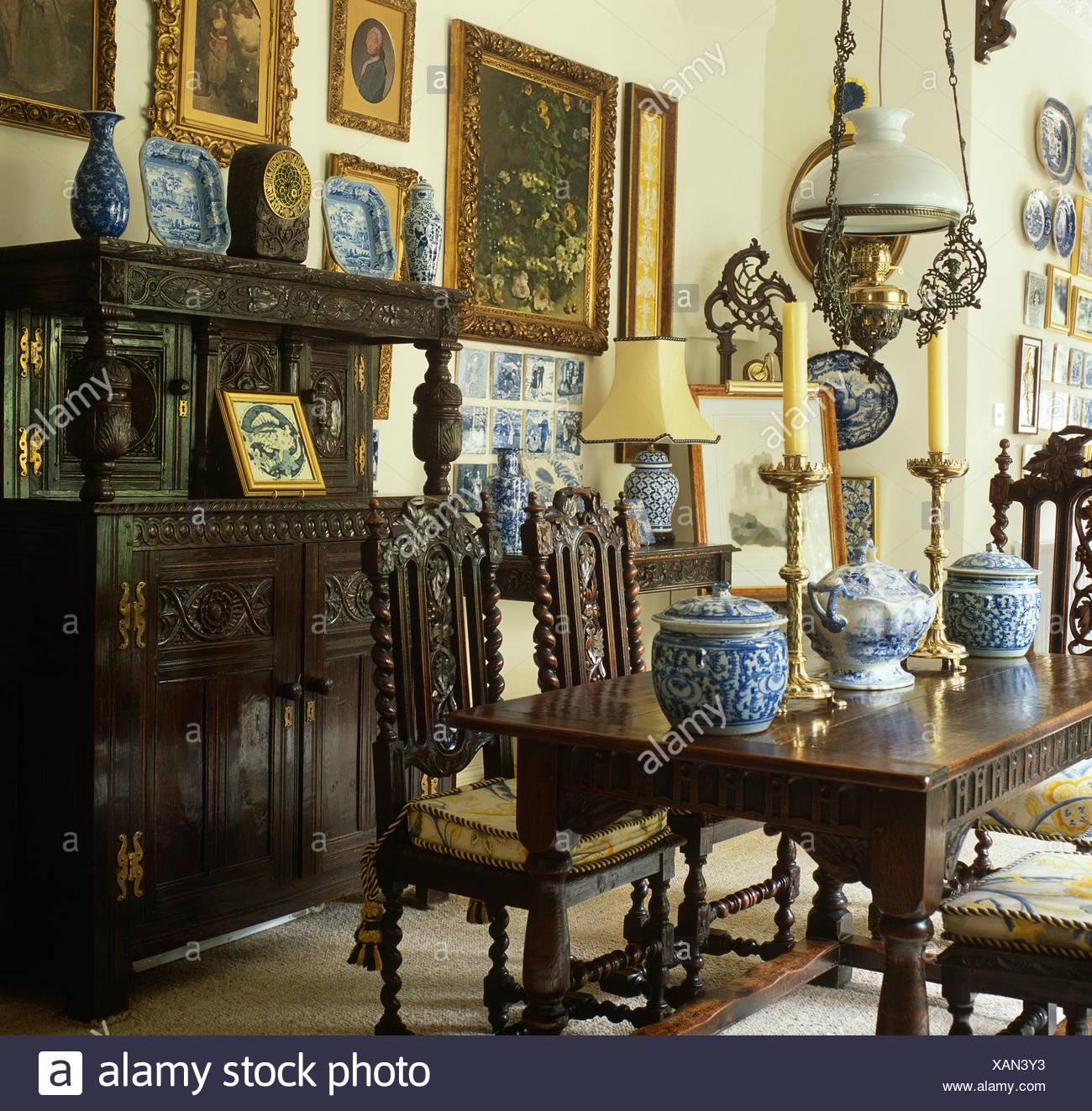 Collection of blue+white china in country dining room with heavy carved oak table and sideboard and Jacobean style chairs Stock Photo