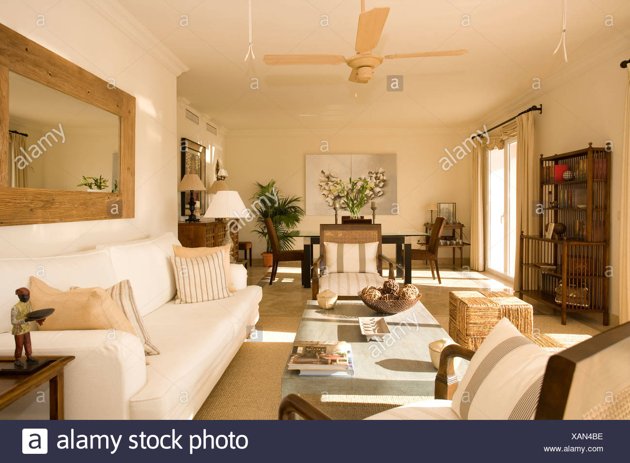 Large Wooden Mirror Above Cream Sofa In Modern Openplan Living And Dining Room With Ceiling Fan Stock Photo Alamy