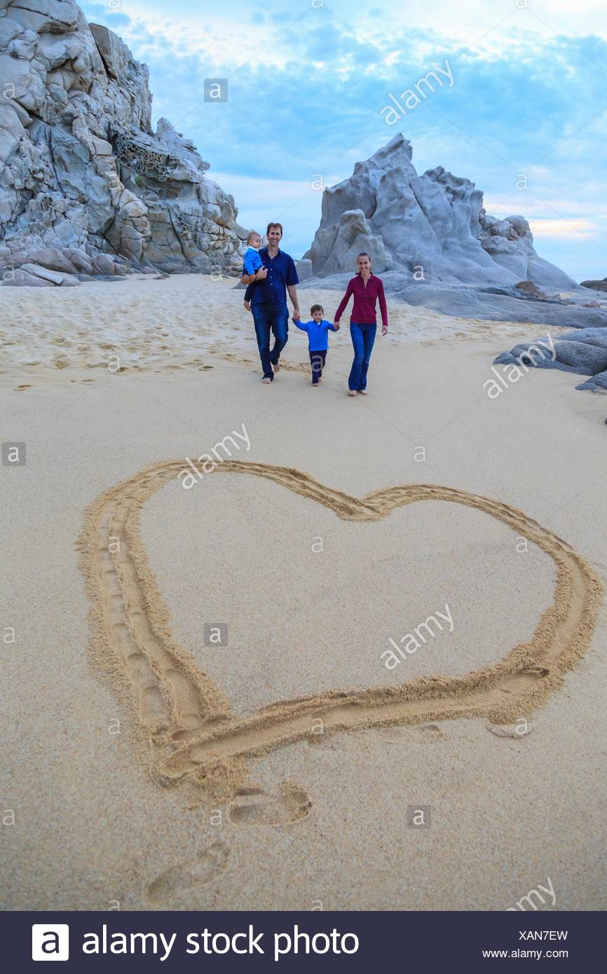 Young family walking on beach, heart shape in foreground - Stock Image