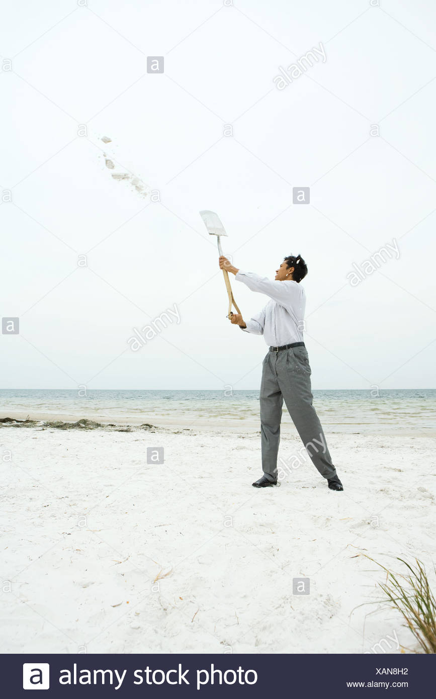 Man at the beach holding up shovel, throwing sand, full length Stock Photo