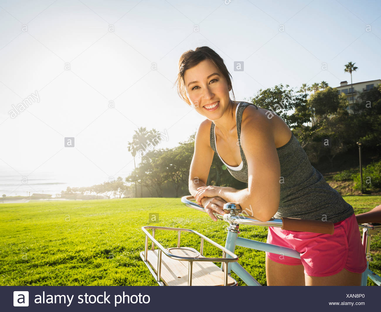 Young woman with bicycle in park - Stock Image