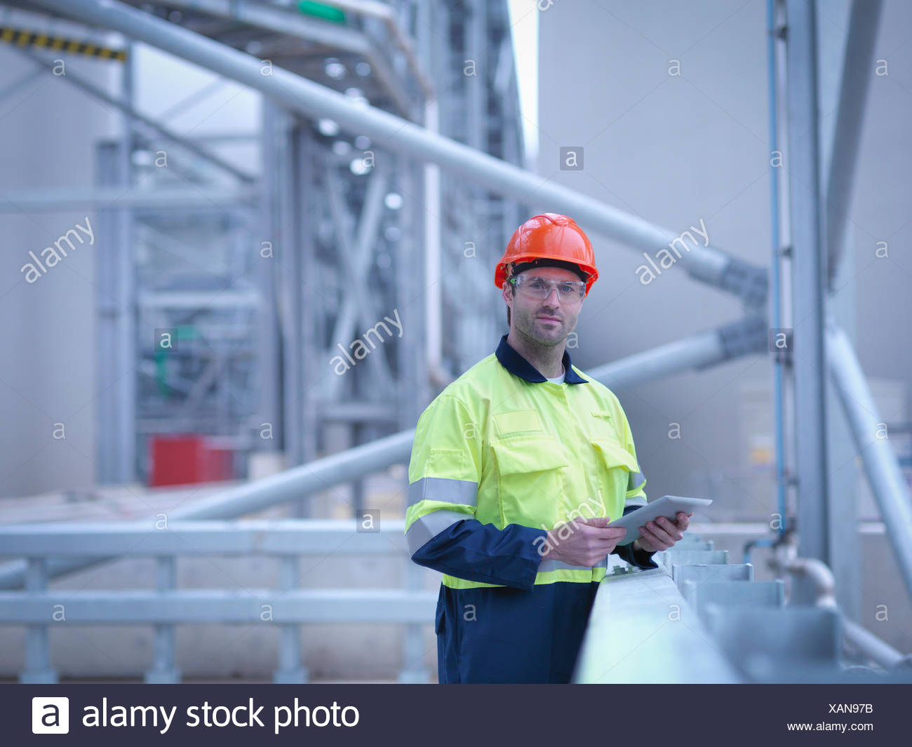 Portrait of worker holding digital tablet at biomass facility - Stock Image