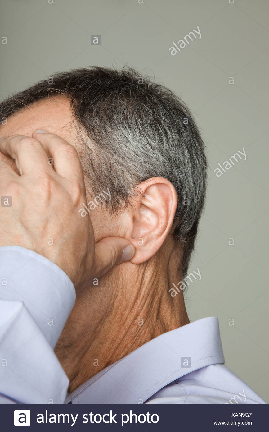 Mature man holding head, cropped - Stock Image