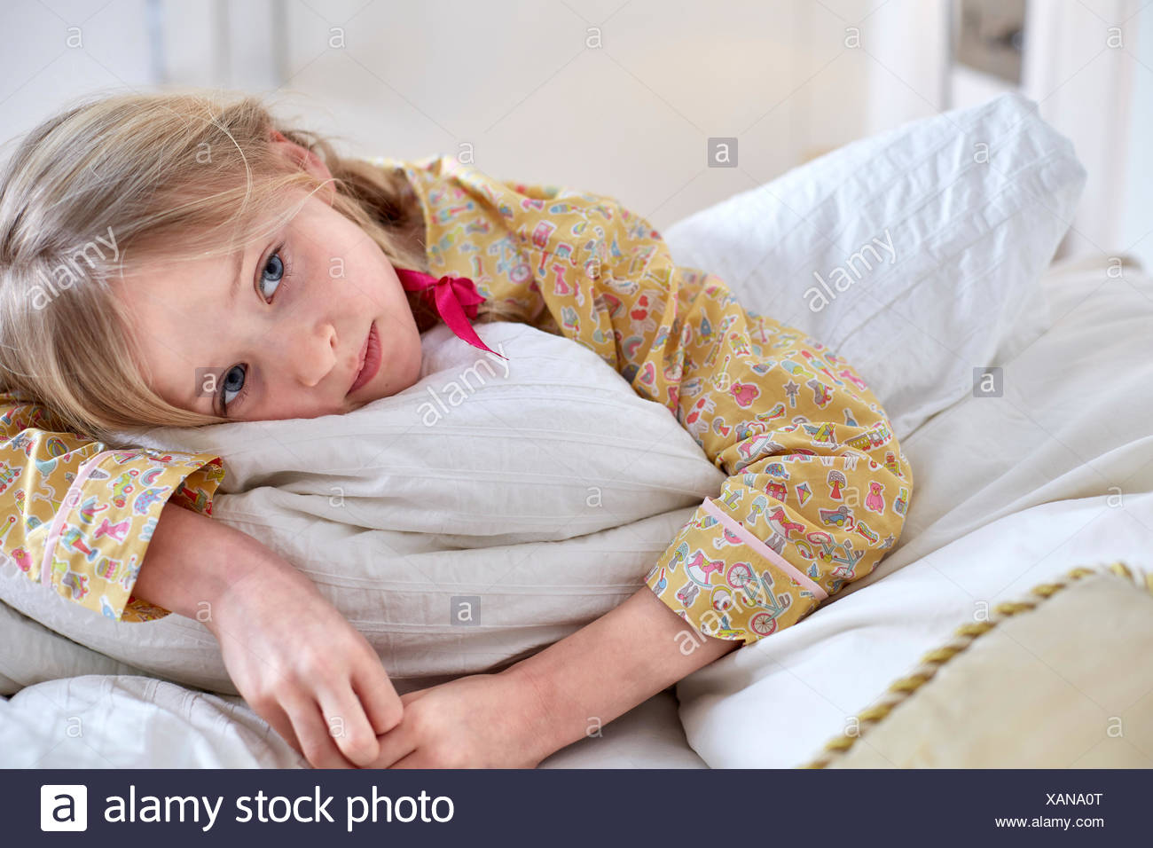 Girl in pyjamas day-dreaming in bed - Stock Image