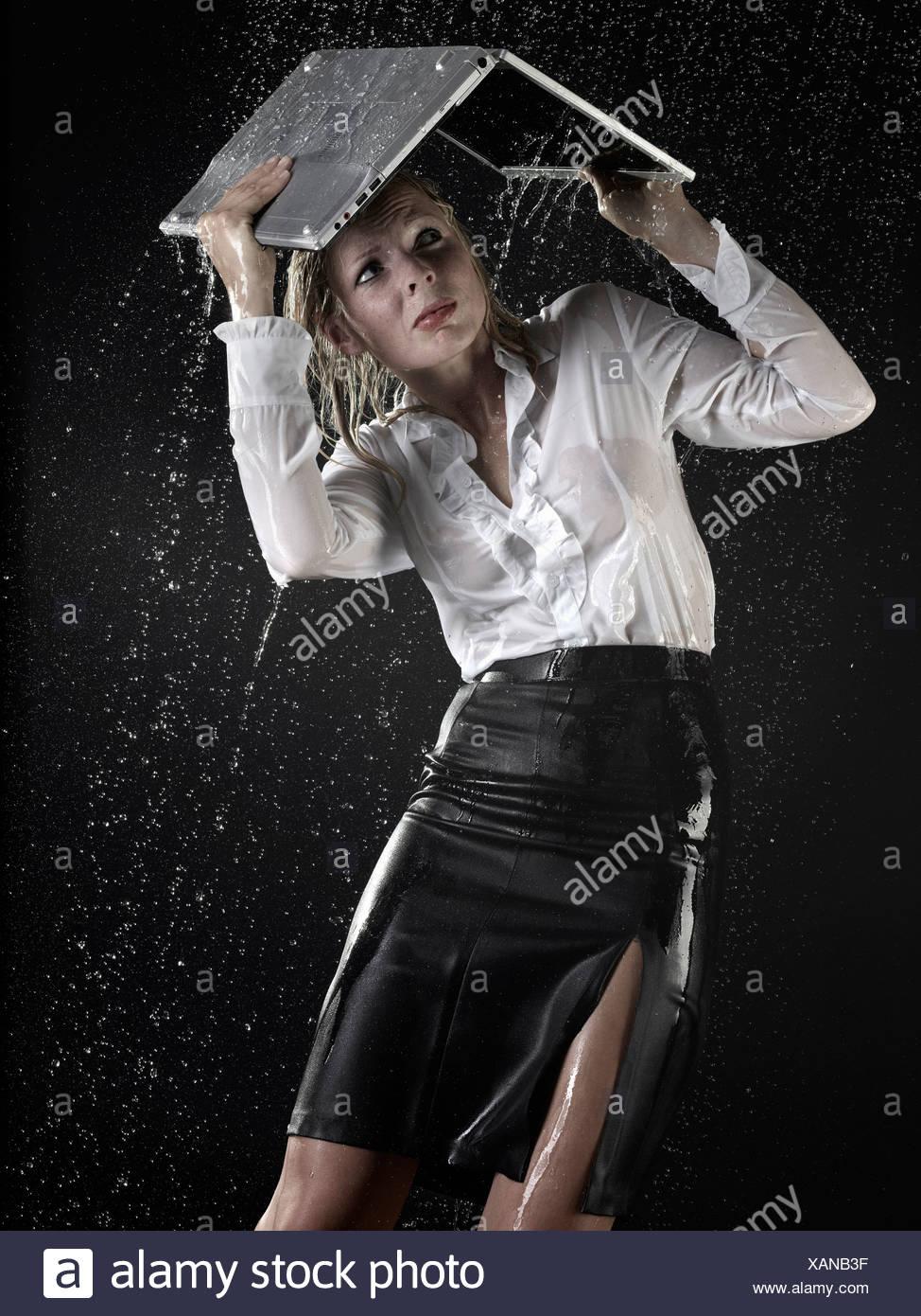 Businesswoman under laptop in rain - Stock Image
