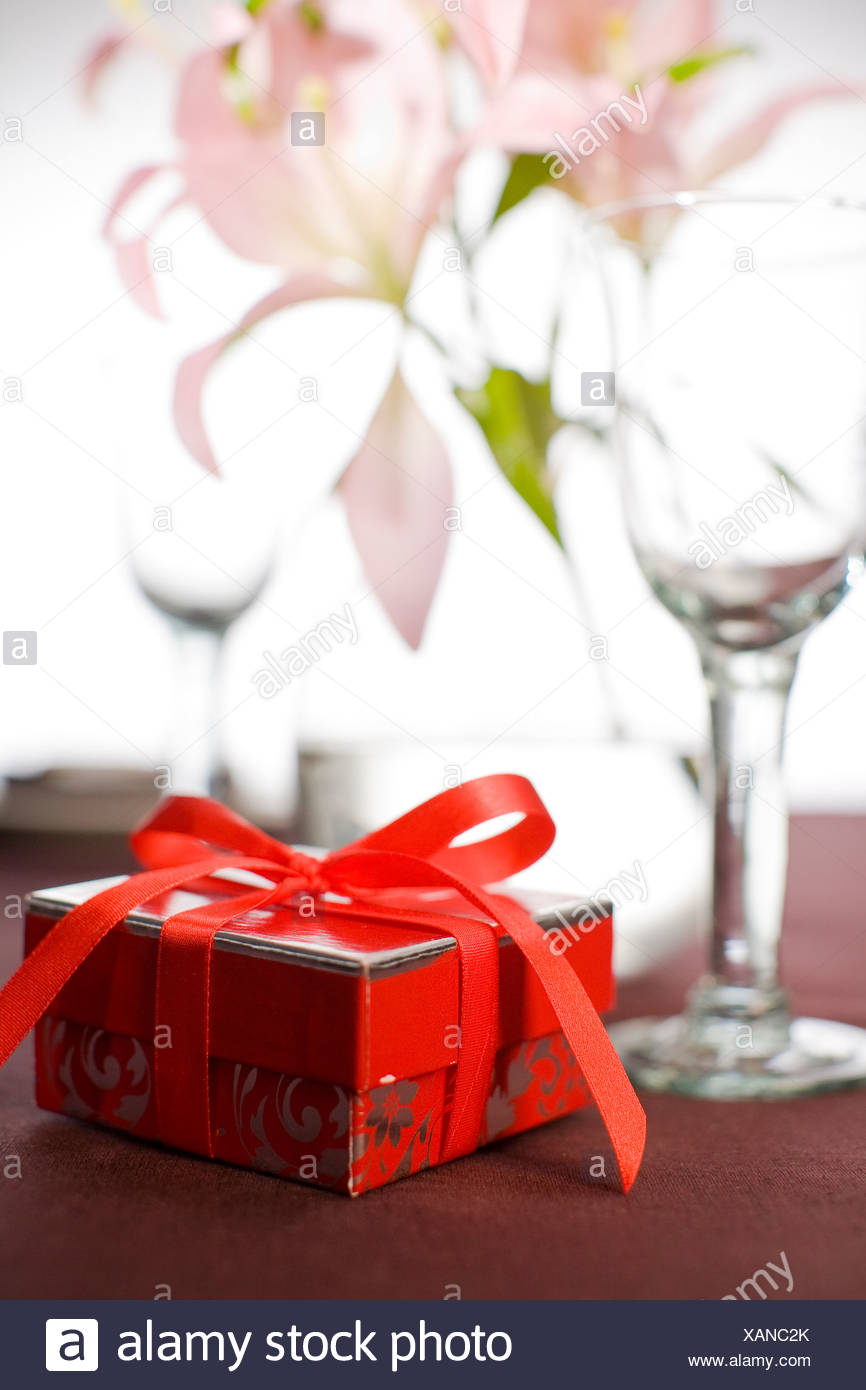 Table laid with a little red gift box. - Stock Image