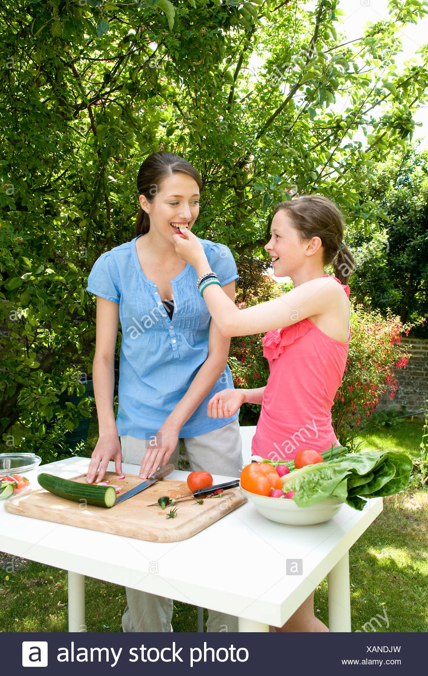 Daughter feeds mother salad, outdoors - Stock Image
