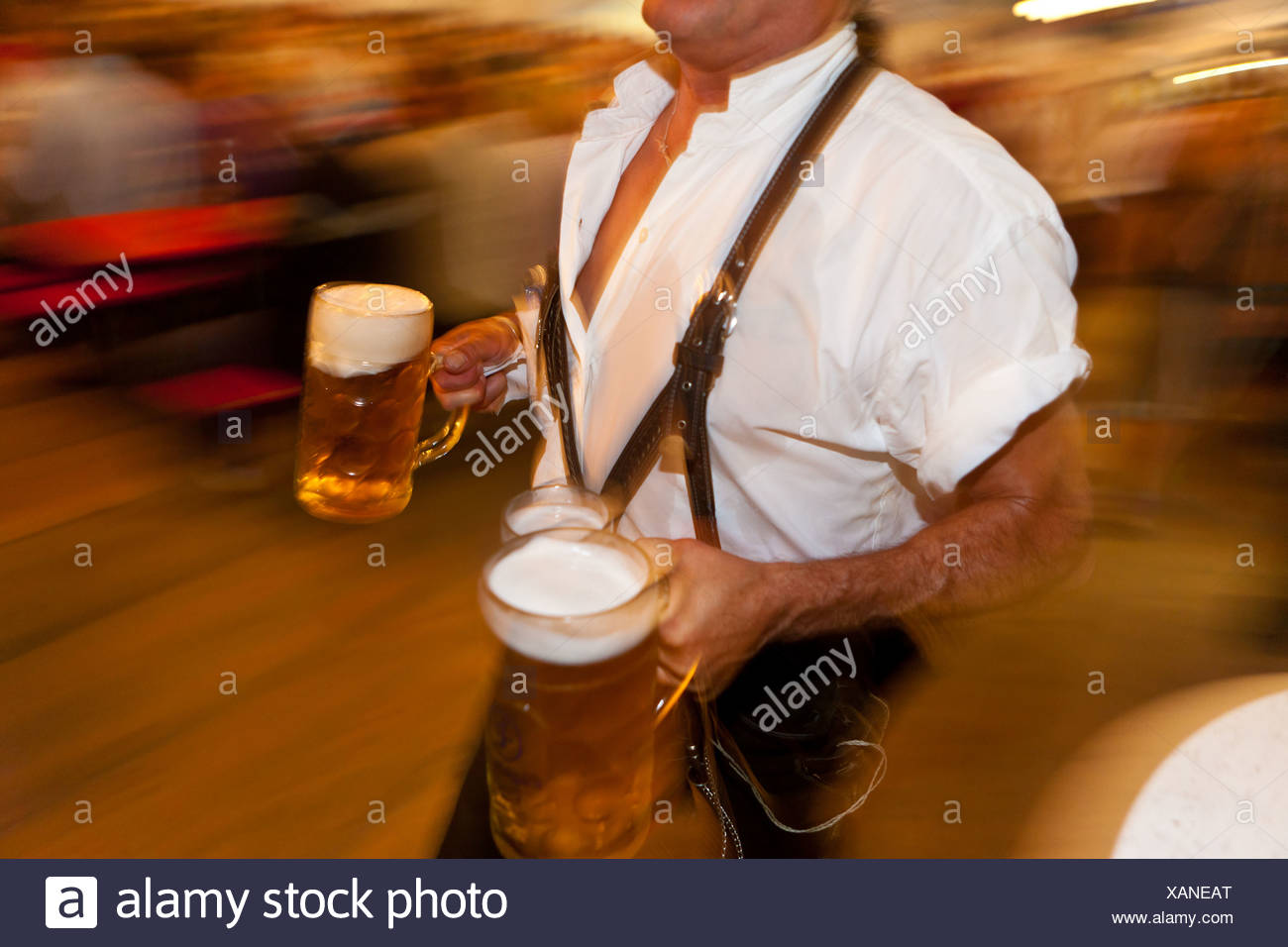 Hurried waiter carrying beer mugs during the opening of the cattle drive in Pfronten, Ostallgaeu, Allgaeu, Bavaria - Stock Image