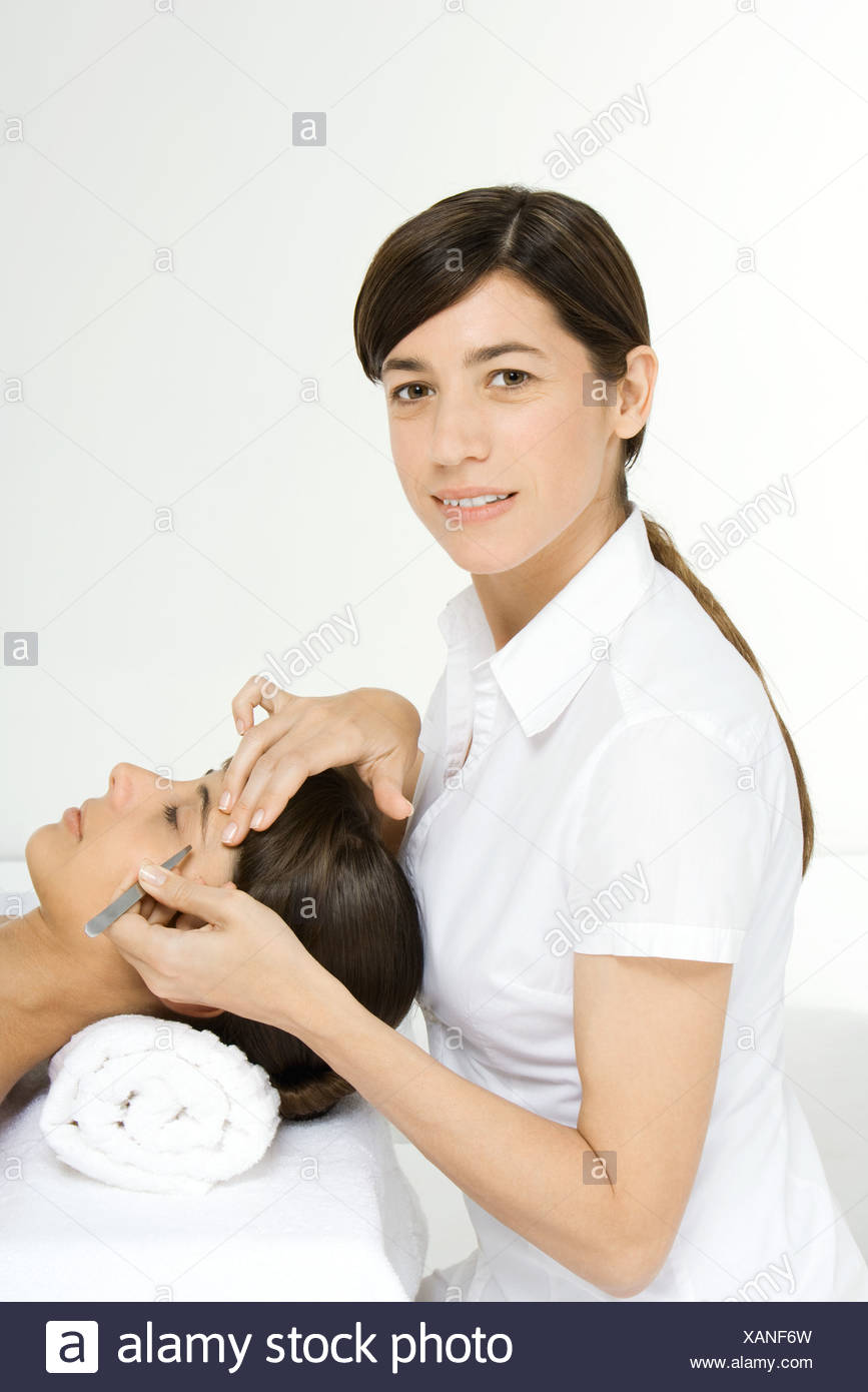 Beautician smiling at camera and plucking a woman's eyebrows - Stock Image