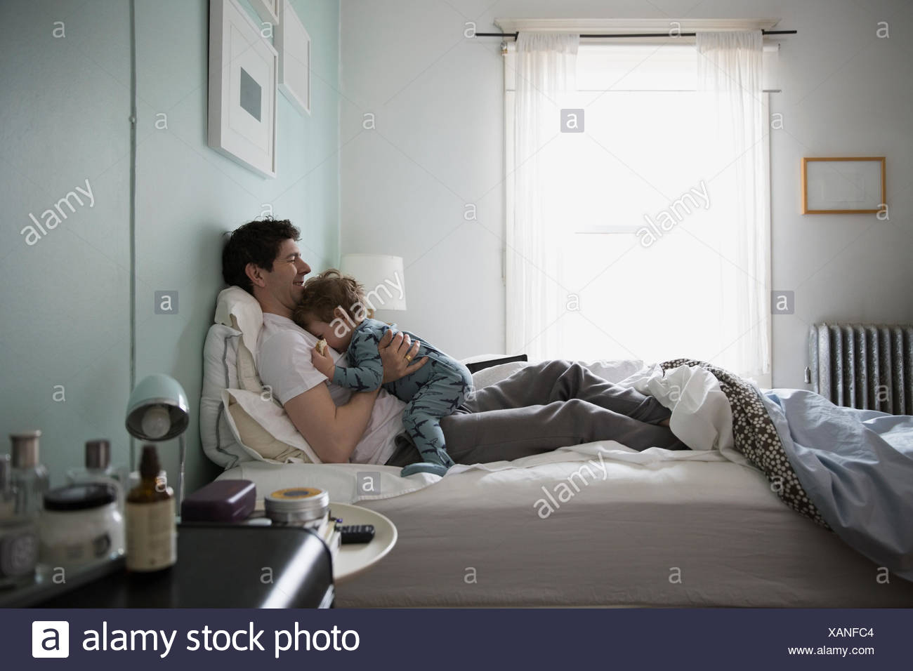 Father cuddling son in pajamas in bed - Stock Image
