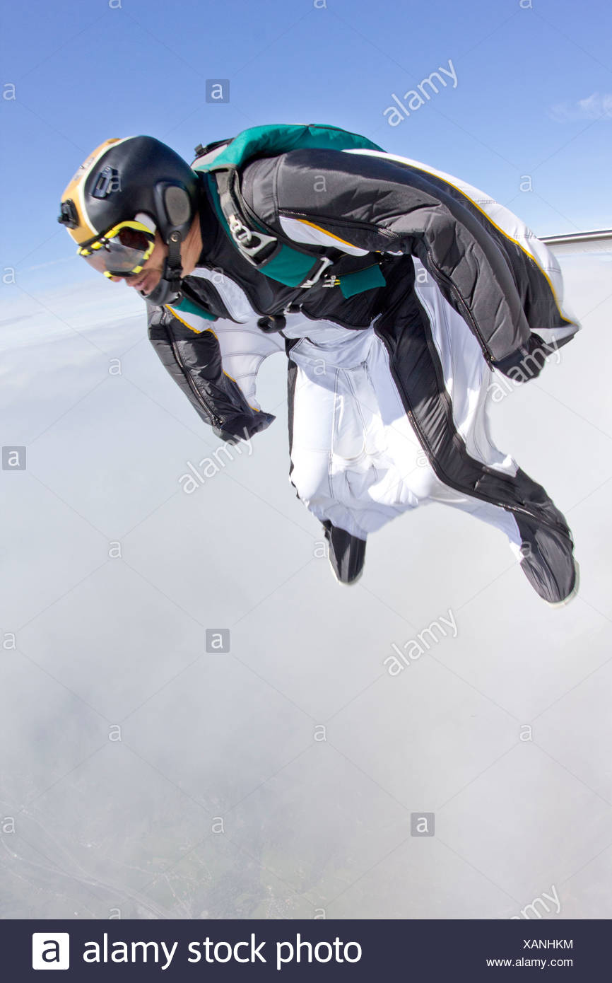 Mid adult man free falling in wingsuit preparing to fly - Stock Image