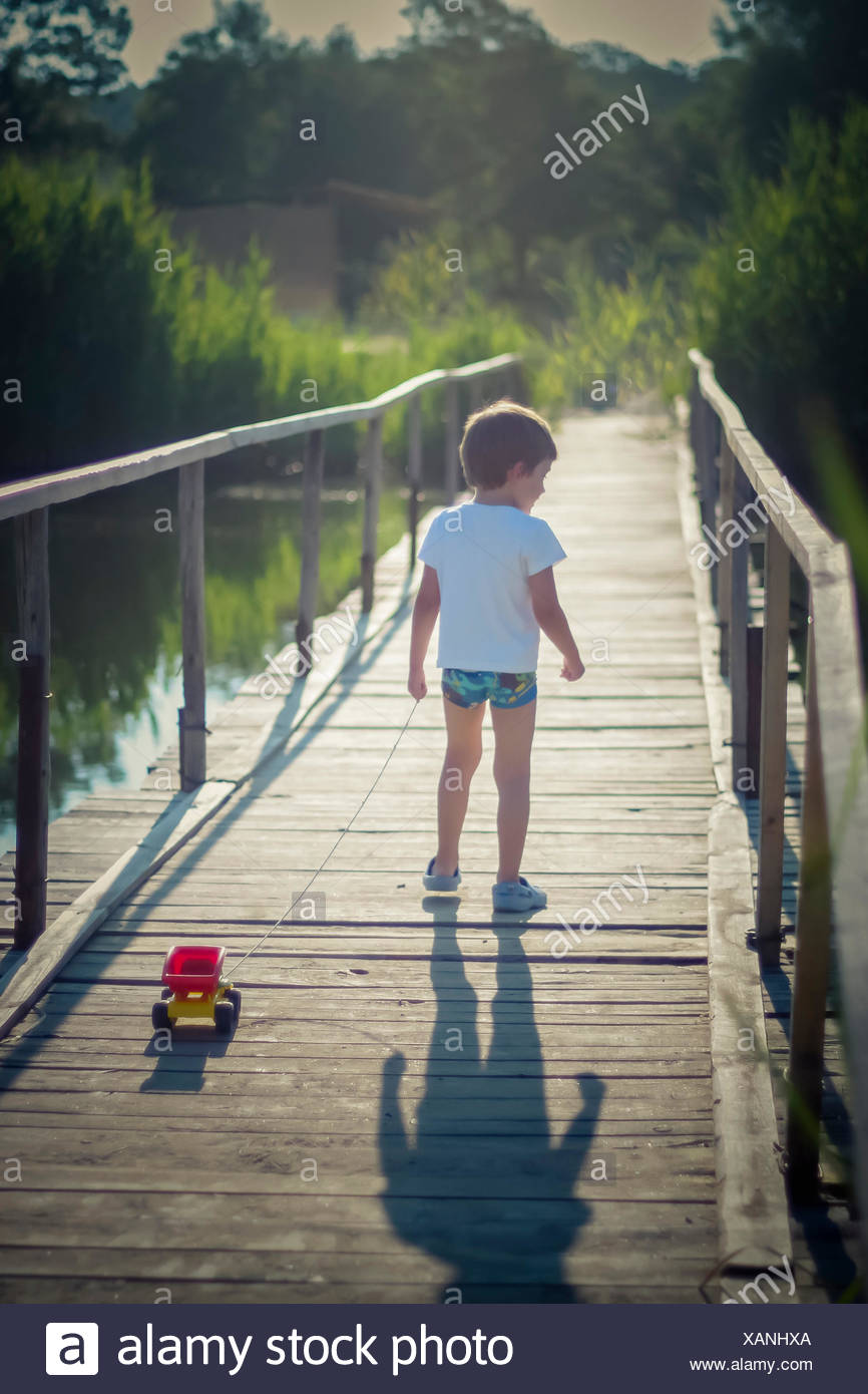 Boy pulling a toy truck across a bridge Stock Photo