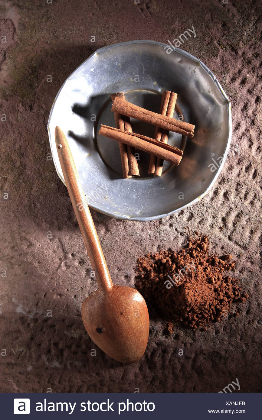 Cinnamon sticks (Cinnamomum) on a metal plate with a wooden spoon and cinnamon powder on a rustic stone base - Stock Image