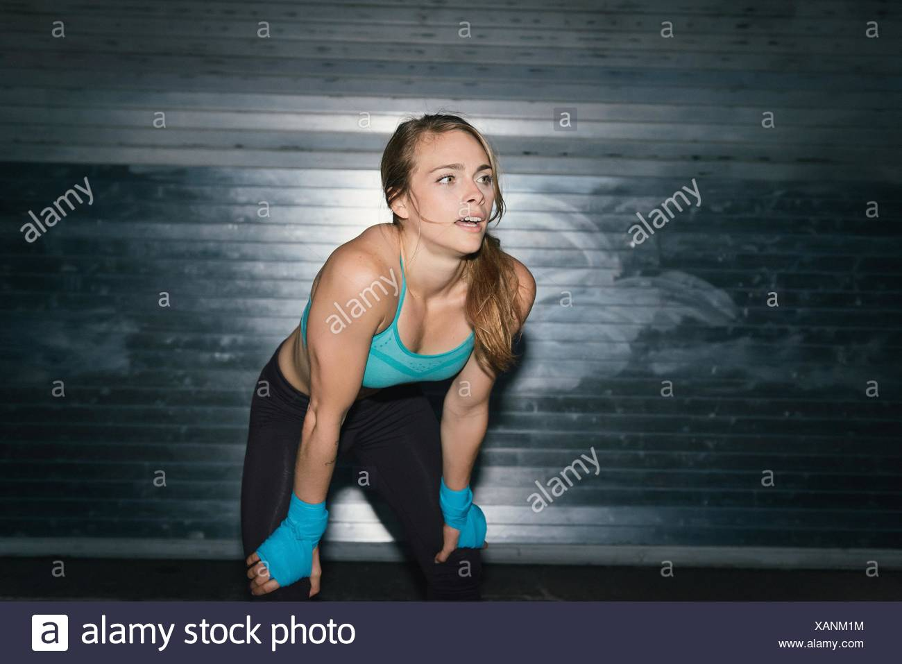 Young woman, working out, hands on knees, outdoors, at night - Stock Image