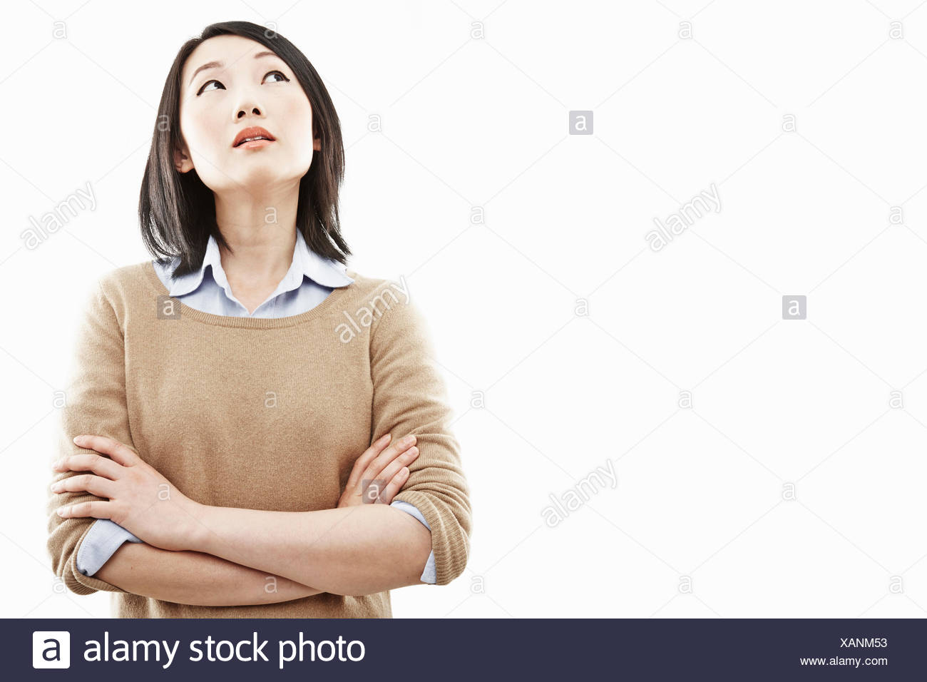 Close up studio portrait of young woman with arms folded - Stock Image