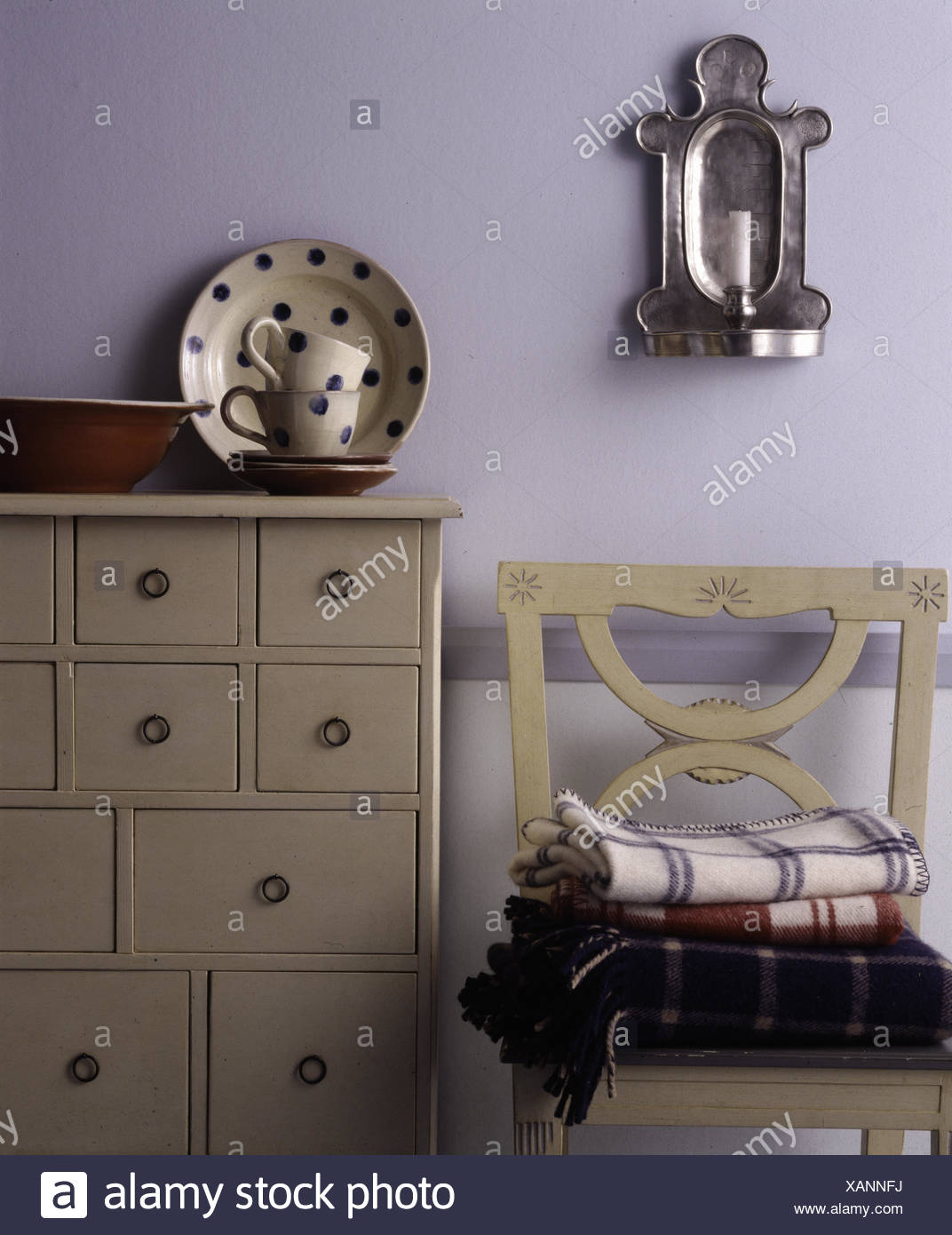 Spotted crockery on cream painted chest of drawers - Stock Image