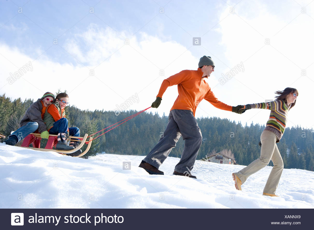 Couple pulling son and daughter  on sled in snow, smiling, side view - Stock Image