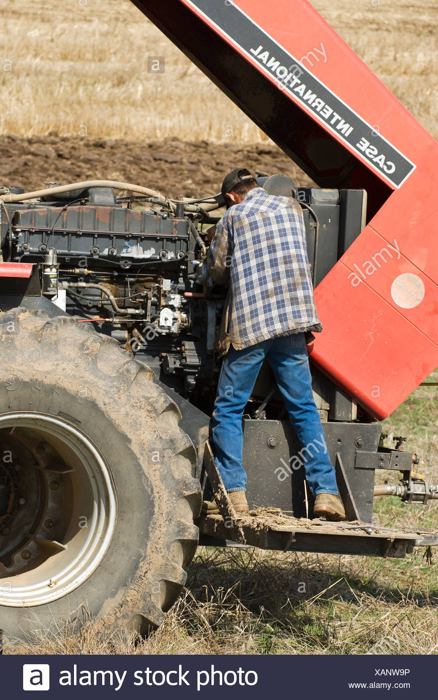 A farmer performs maintenance on a tractor in the field during planting season / near Pullman, Palouse Region, Washington, USA. - Stock Image
