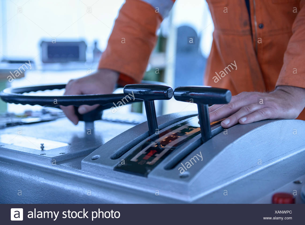 Worker manning tugboat controls - Stock Image