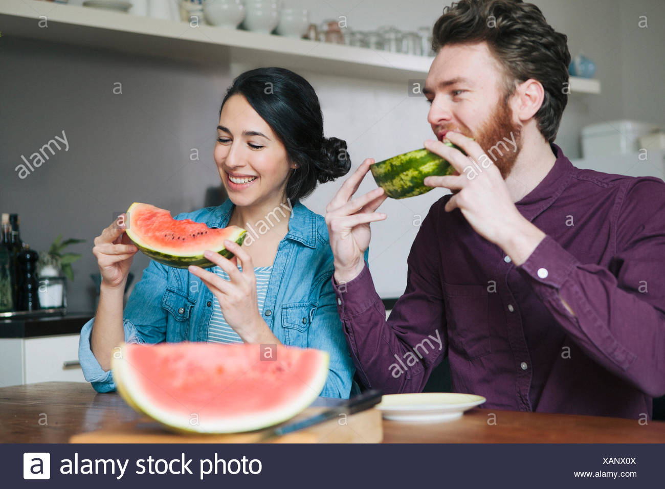 Happy Young Couple Eating Watermelon At Kitchen Table Stock