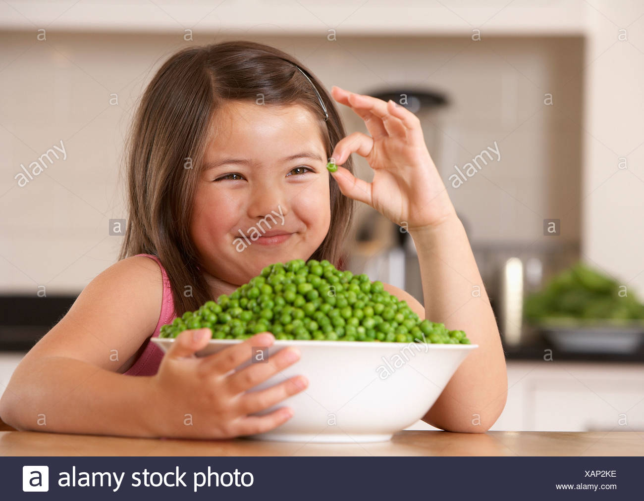 Young girl in kitchen with a bowl of green peas holding one single pea and smiling - Stock Image