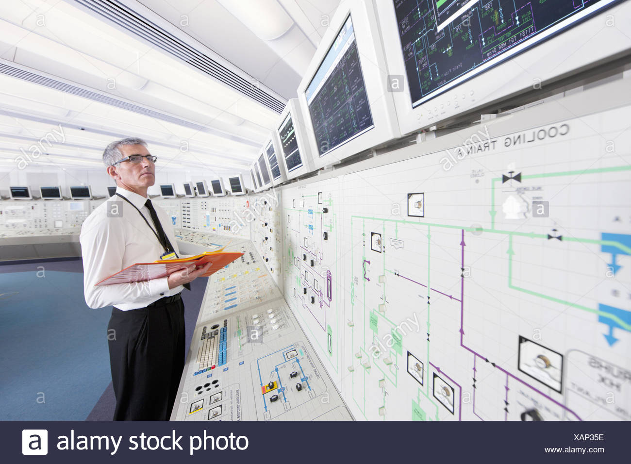 Engineer looking up at monitors in control room of nuclear power station Stock Photo