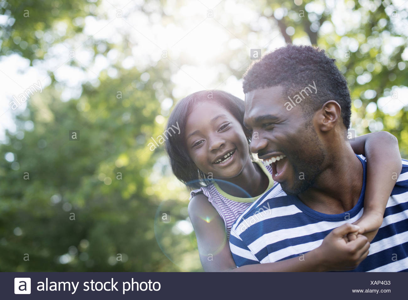 A man giving a child a piggyback in the shade of trees on a summer day Stock Photo