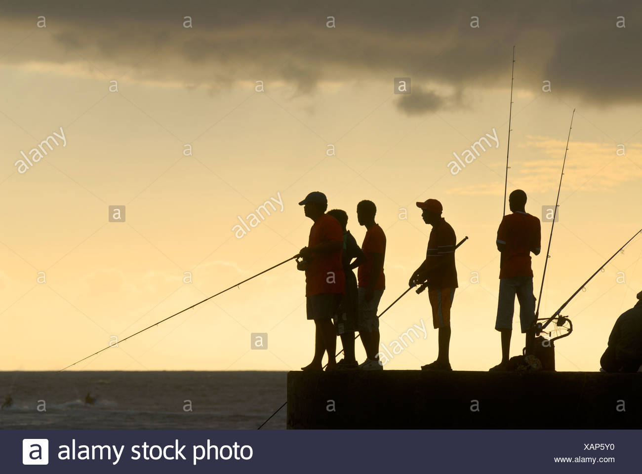 Silhouettes of recreational anglers on the pier of St. Gilles de Baines, La Reunion, Indian Ocean - Stock Image