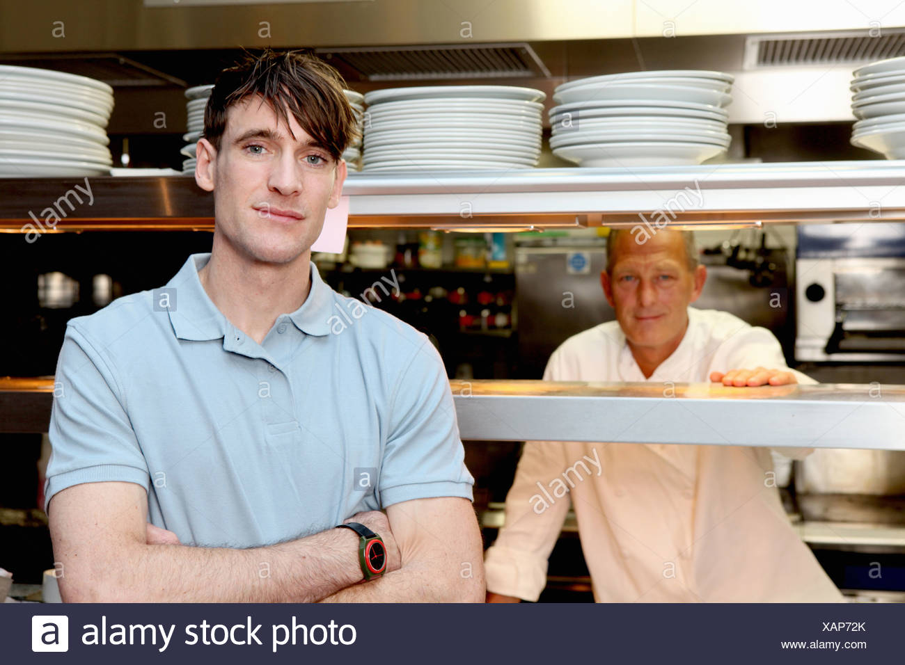 Chef and waiter in kitchen - Stock Image
