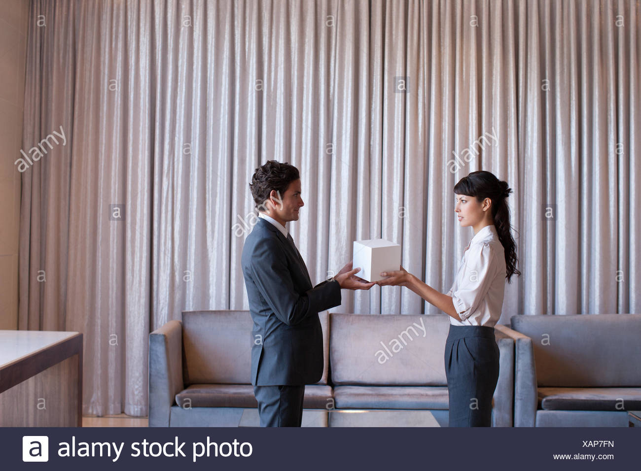 Business people holding white cube in hotel lobby - Stock Image