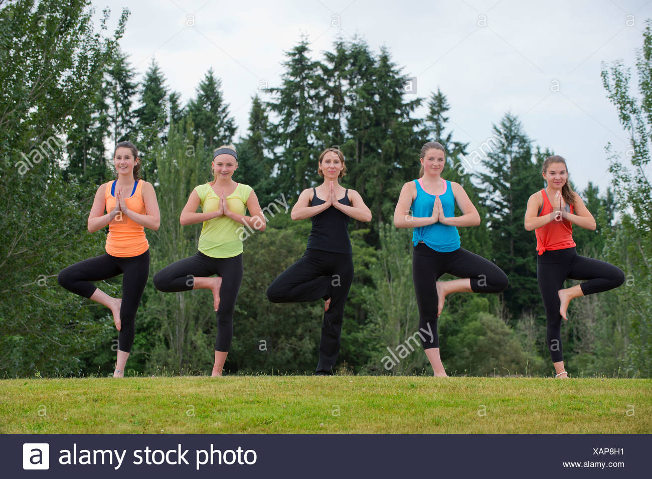 Teenage girls and yoga tutor doing tree poses - Stock Image