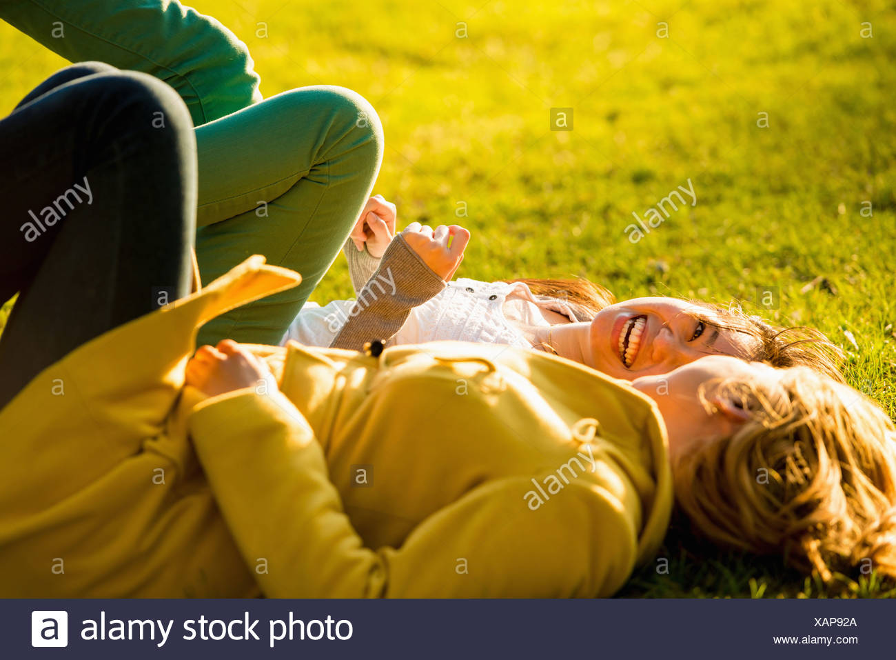 Two young women lying back in park - Stock Image