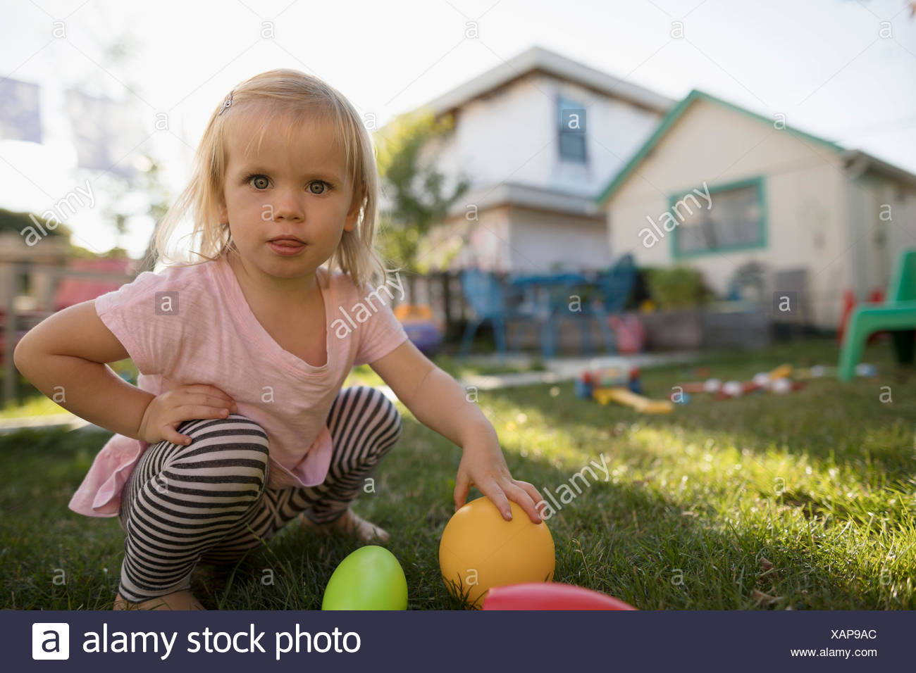 Portrait curious blonde toddler girl playing with toys in backyard - Stock Image