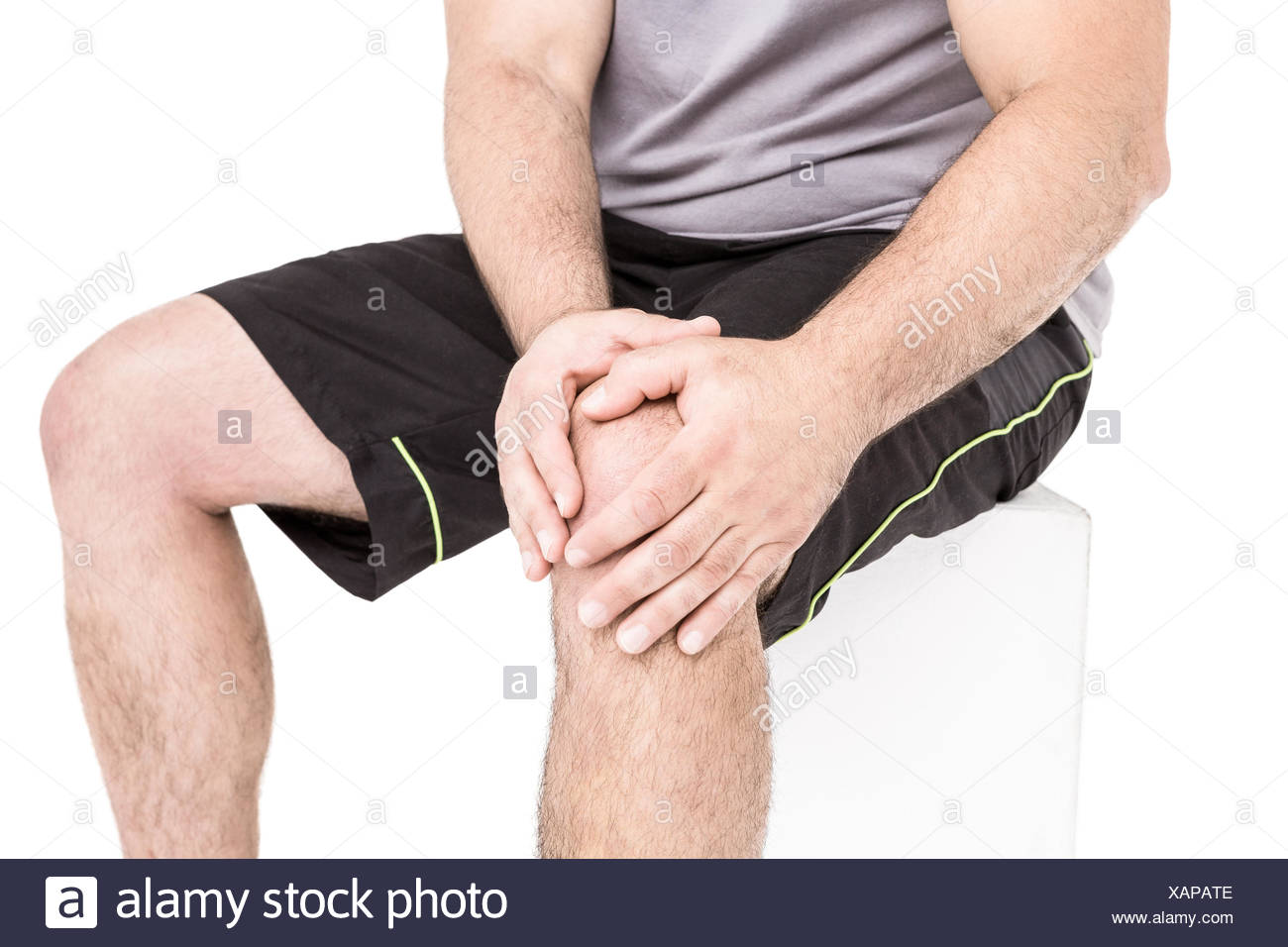 Athlete clutching knee in excruciating pain - Stock Image