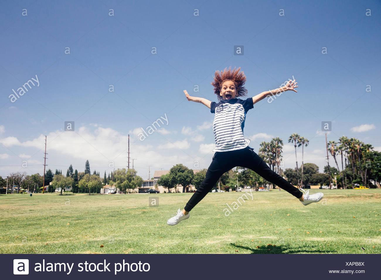 Schoolgirl doing star jump on school sports field - Stock Image