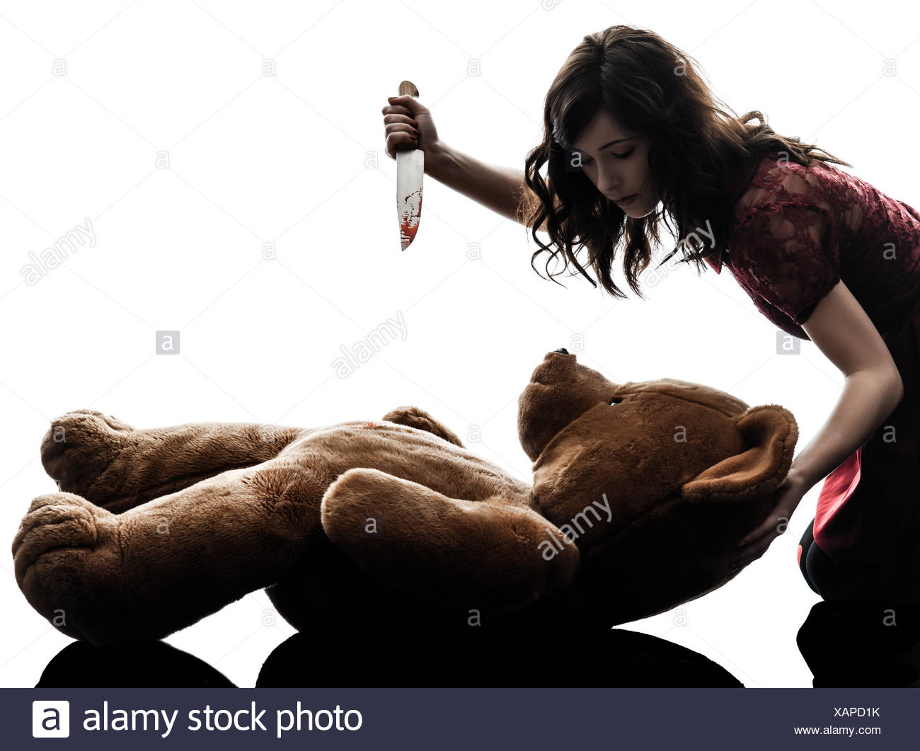 one caucasian strange young woman killing her teddy bear  in silhouette white background - Stock Image