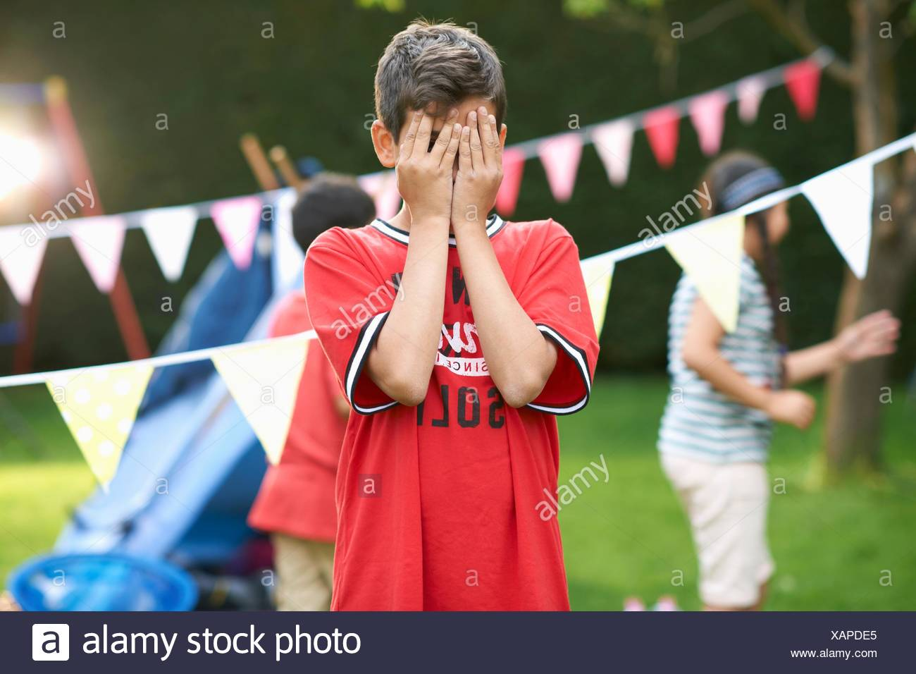 Boy covering his eyes for hide and seek with sister and brother in garden - Stock Image
